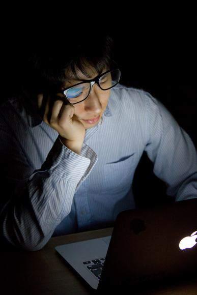 台風で帰宅できずに残業しうなだれる男性 大川竜弥