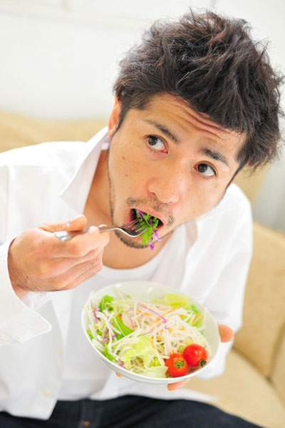 サラダを食べる男性