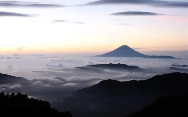 雲の上に顔を出した朝焼けの富士山