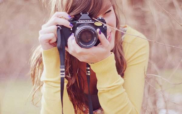 笑顔でカメラのファインダーを覗く女性