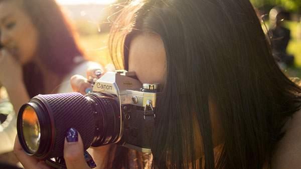 大きなレンズのCanonカメラを構える女性