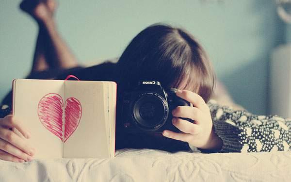 ベッドに寝そべって写真を撮るカメラ女子