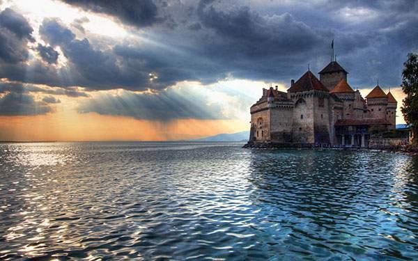 雲間から差し込む光と海とお城