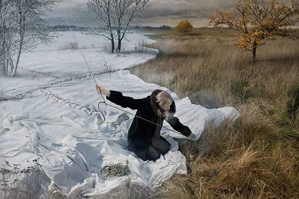 布を縫うようにして冬の景色を作る女性