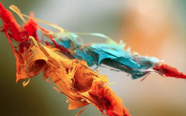 空中に浮かぶオレンジと青の繊維上の物体