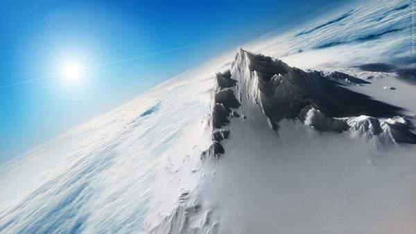 雲の上から撮影した雪山と太陽