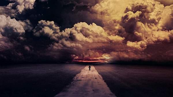 厚い雲とまっすぐな道の真ん中に立つ男