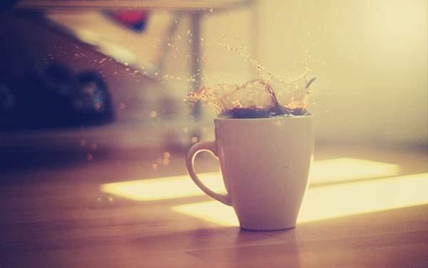 カップから勢いよく溢れるコーヒーを撮影した写真
