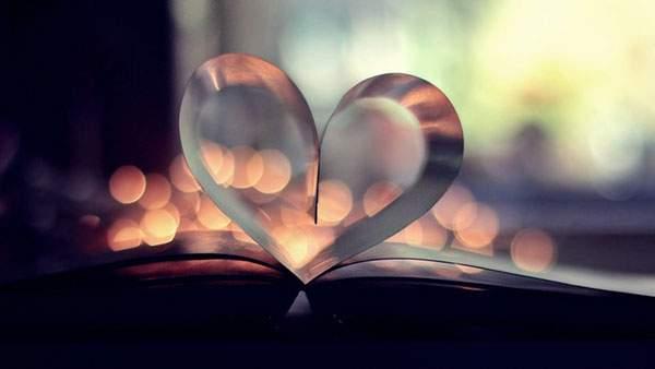 光のボケがロマンチックな本のページで出来たハートの壁紙