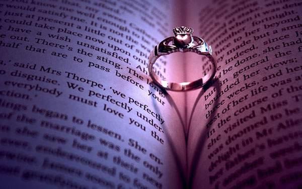 指輪と本に落ちたハート型の影のロマンチックな写真