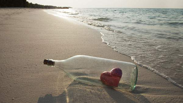 流れ着いたハートの入ったボトルのロマンチックな写真