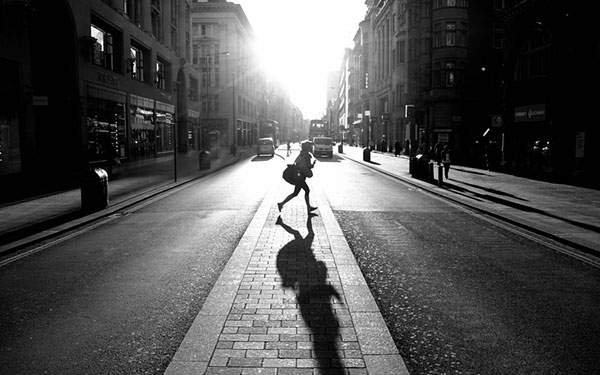 街を走る人を逆光で撮影したモノクロ写真