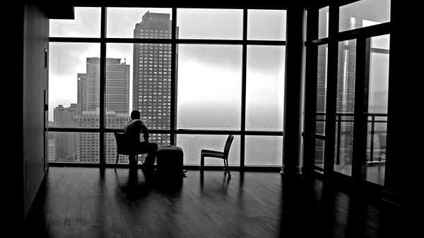 部屋の窓からビルを見つめる人を撮影したモノクロ写真壁紙