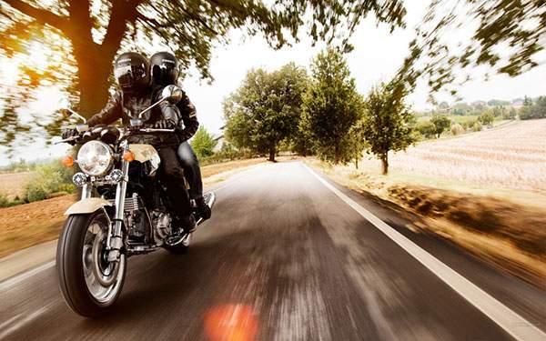 Ducatiのバイクで街を走るバイカーの壁紙画像
