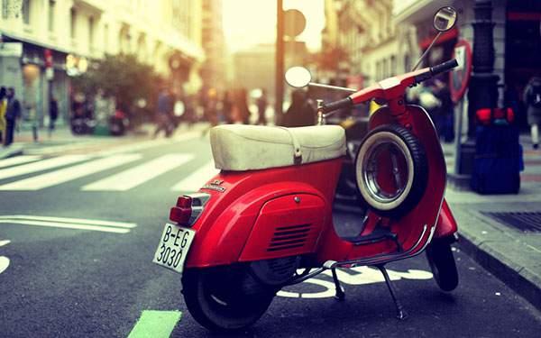 街角に止めてあるしゃれた赤いバイクの画像