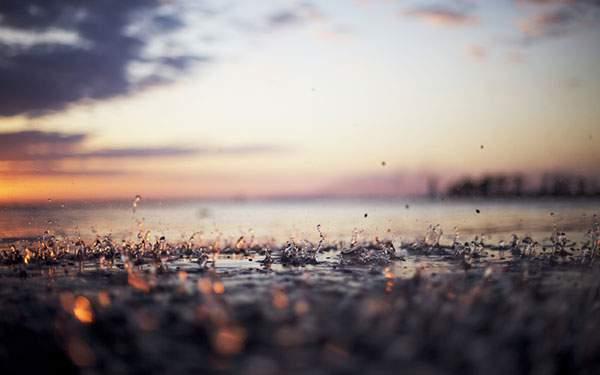 雨粒が跳ねる水面と夕日の綺麗な写真
