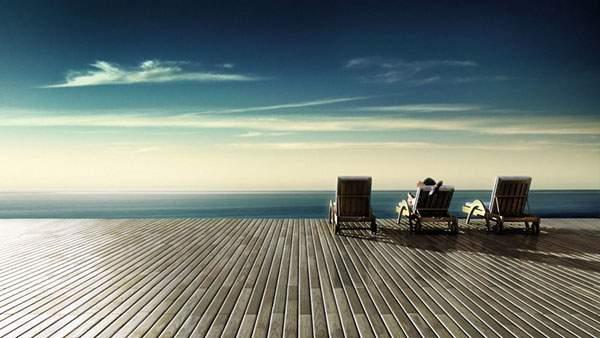 青い空と青い海が視界いっぱいに昼がるビーチチェアのある風景