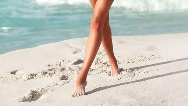 裸足でビーチを歩く女性を撮影した写真