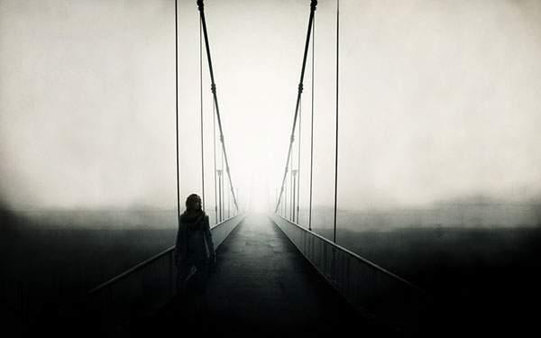 霧の中に消えていく吊り橋に佇む男性を撮影したモノクロの写真壁紙