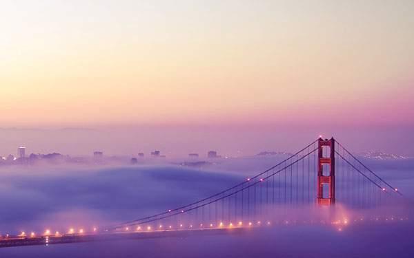 霧と夕焼けに染まったゴールデンゲートブリッジの美しい写真壁紙
