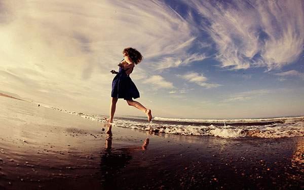 ビーチの波打ち際を走る女性の美しいな写真壁紙