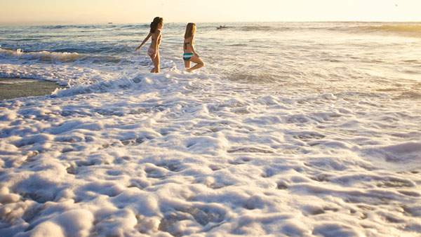 波と二人の水着の女の子の綺麗な写真壁紙