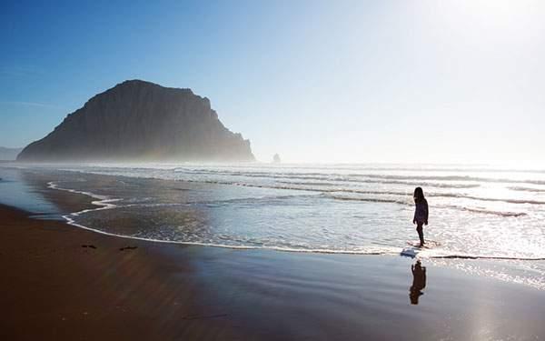 爽やかな空と砂浜を歩く女性の写真画像