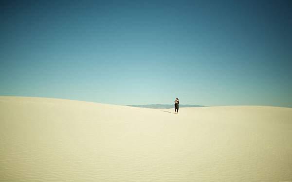 砂漠にたったひとりで佇む女性の綺麗な写真画像