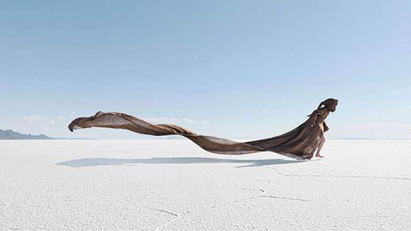 風を受けてローブをたなびかせる女性の幻想的な写真