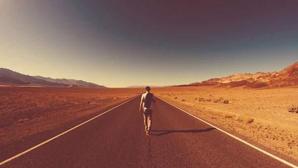 砂漠の真ん中のまっすぐな道を歩く男性の写真壁紙