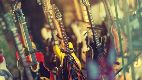 ショーケースに並んだたくさんのギターの写真の壁紙