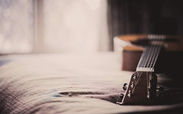 ベッドの上に置かれたアコースティックギターの高画質な壁紙画像