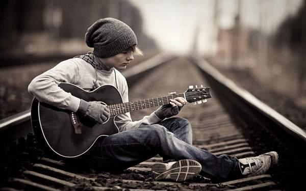 線路の上に座ってアコースティックギターを引く男性のおしゃれな写真