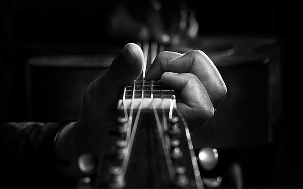 ギターの弦を抑える指をアップで撮影したクールなモノクロ写真