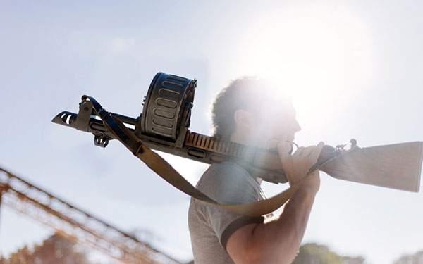 機関銃を肩に担いだ男を逆光で撮影した写真壁紙