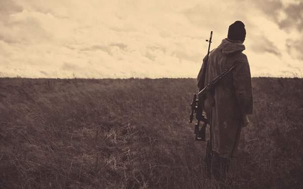 ライフルを肩にかけて草原に佇む男の壁紙画像