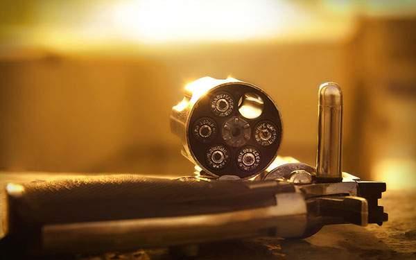 夕日を受けて光るリボルバー銃の弾倉と弾丸の壁紙画像