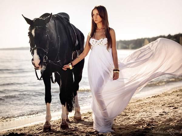 黒い馬を連れて海辺を歩く白いドレスを着た女性