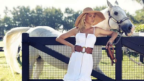 フェンスにもたれかかる女性と白馬を撮影した爽やかな写真画像