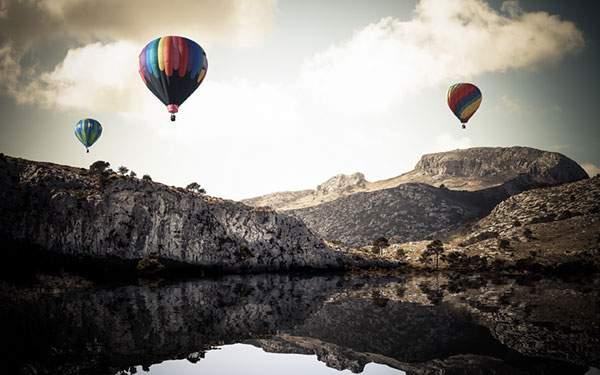 岩山の上を飛ぶ3つのカラフルな熱気球