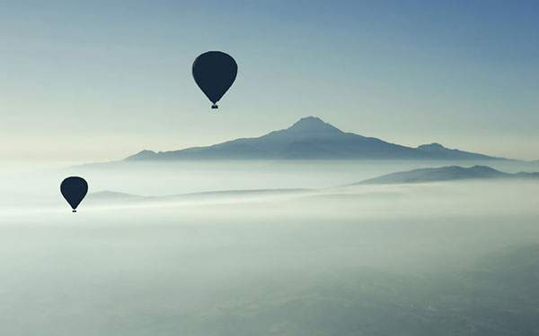 遠くに見える霞がかった山と熱気球のシルエット