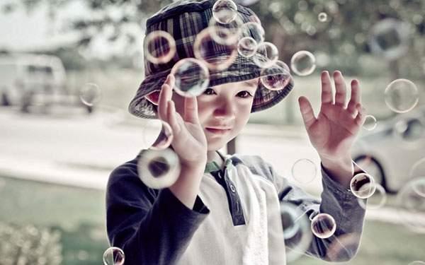 楽しそうにシャボン玉を見つめる男の子の写真