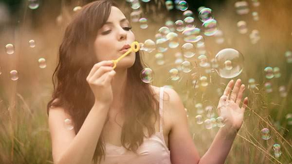たくさんのシャボン玉を作る女性のキレイな写真画像