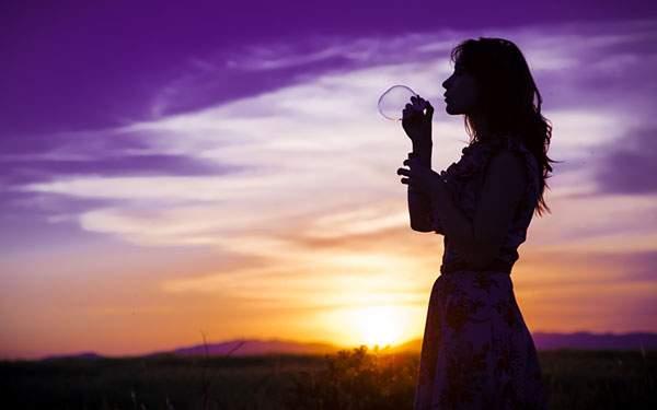 夕日の中でシャボン玉を作る女性のシルエットを撮影した綺麗な写真