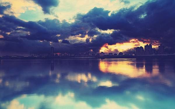水面に写る対岸のビル街と夕焼けの空の写真壁紙