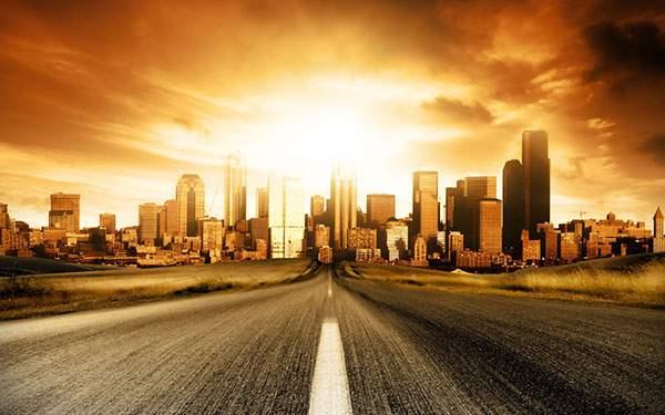 夕焼けの街並みに向かう高速道路の写真画像
