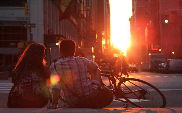 夕日の差し込む街並みと座り込んだカップルの写真壁紙