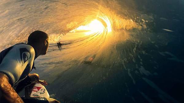 サーフィンをする男性と波の内側から見える夕日の美しい写真