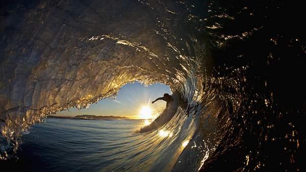 波のトンネルをくぐり抜ける瞬間の爽快なサーフィンの写真