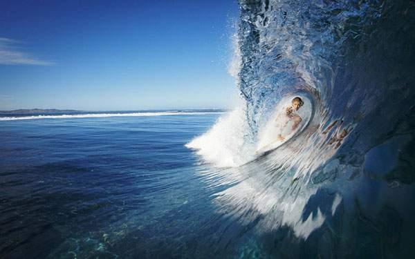 真っ青な波の中を突き進むサーファーの綺麗な写真壁紙